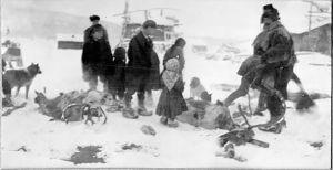 Svartvitt fotografi: skoltsamer på vintern, renhorn i snön, vuxna och barn.