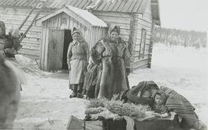 Svartvitt fotografi av skoltsamer på vintern.