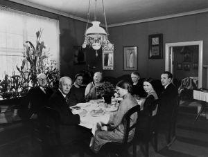 Säveltäjä Erkki Melartin ja vieraita pöydän ympärillä hänen huvilassaan Pukinmäessä 1930-luvulla.
