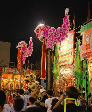 Ljusröda kinesiska enhorningar och lejondansare.
