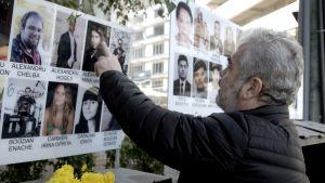 Eugen Iancu osoittaa poikansa kuvaa muistotaulussa