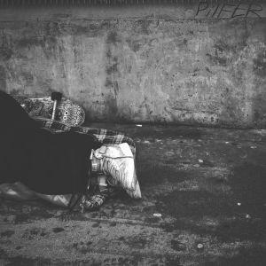 Henkilö makaa likaisella kadulla, vain jalat näkyvät.