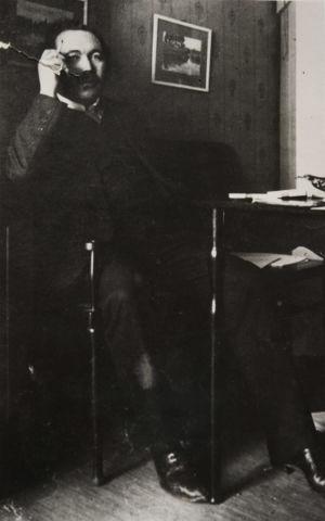 Runoilija Eino Leino tupakoi työhuoneessaan maaliskuussa 1912.