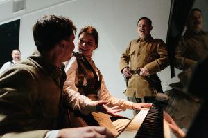 Pianon ääressä nauravia ihmisiä: vasemmalta oikealle näyttelijät Santtu Karvonen, Pyry Nikkilä, Roosa Söderholm ja Robin Svartström.