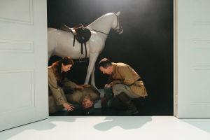 Mies ja nainen kumartuvat hevospatsaan juurella makaavan kuolleen miehen puoleen. Rooleissa Roosa Söderholm, Robin Svartström ja Pyry Nikkilä.