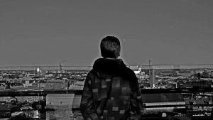 mies parvekkeella Helsingin kattojen yllä