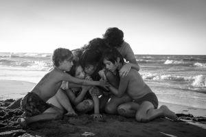 Lapset ja lastenhoitaja halaavat toisiaan meren rannalla. Kuva Alfonso Cuarónin elokuvasta Roma (2018).