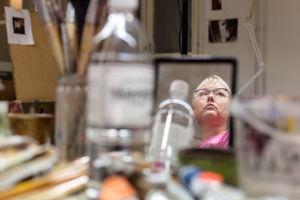 Elina Lehtoranta pöydällä olevan peilin kautta kuvattuna. Pöydällä näkyy maalaustarvikkeita.