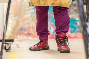 Elina Lehtorannan jalat lattian tasosta kuvattuna. Elinalla on jalassaan punaiset nahkakengät, vasemman kengän nauhat ovat auki.