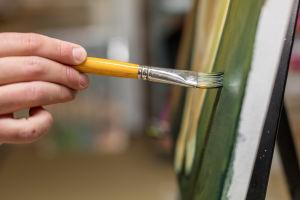 Lähikuva kädestä, joka maalaa pensselillä vihreää väriä tauluun.