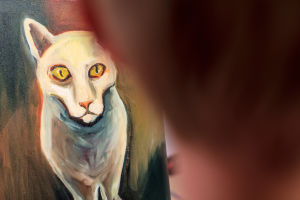 Yksityiskohta Elina Lehtorannan maalaamasta kissataulusta. Etualalla Elina epäterävänä.