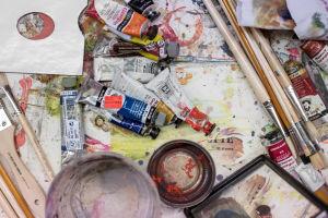 Maalaustarvikkeita, värejä, pensseleitä ja kuppeja sekaisin pöydällä.