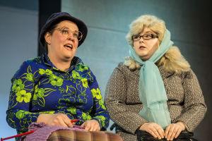 Två kvinnliga skådespelare på scen. Den ena av dem sitter och stickar.