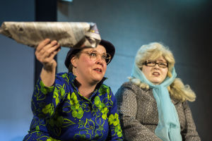 Två kvinnliga skådespelare på scen. Den ena av dem viftar med en dagstidning.