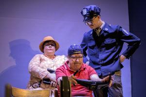 Tre skådespelare på scen. Den ena av dem håller i en ratt. En är utklädd till polis