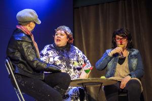 Tre kvinnliga skådespelare på scen. De verkar spela att de sitter i en bar.