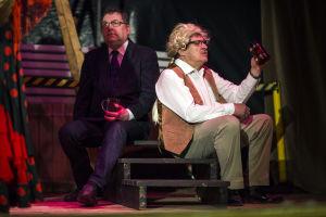 Två manliga skådespelare på scen. De håller i var sin ölmugg.