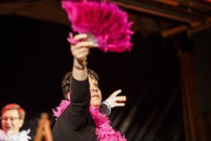 Kvinnlig skådespelare sträcker ut handen med en pink solfjäder.