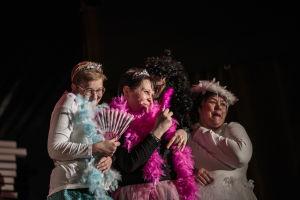 Tre kvinnliga skådespelare på scen. De har solfjäder, fjäderboår och tiaran på sig.