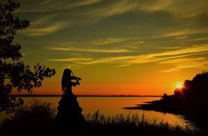 viulua soittavan naisen siluetti veden äärellä auringonlaskussa