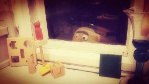 lelu kurkistaa ikkunasta sisään
