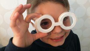 Poika päässään kierrätysmuovista askarrellut tutkijan lasit