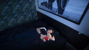 Risto Kuusisto nukkuu sängyssä pehmonalle kainalossa.