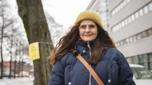 Liisa Vihmanen puistossa, hymyilee ja katsoo kameraan.