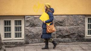 Nainen kävelee kadulla keltainen kyltti kainalossaan.