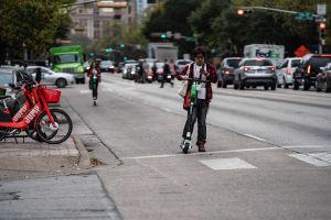 En gata i Austin i Texas. I förgrunden till vänster parkerade elsparkcyklar. På gatan står en person med sin sparkcykel. I bakgrunden en kvinna på en sparkcykel, bilar och människor.