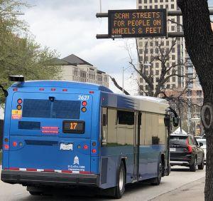 I förgrunden en blå buss på en gata i Austin i Texas. I hakgrunden höghus.