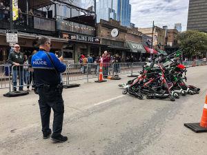 En hög med elektriska sparkcyklar på en gata i Austin i Texas. En polis fotograferar med mobiltelefon.