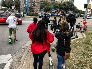 Personer med sparkcyklar på en trottoar i Austin.