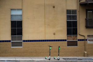 Två  parkerade sparkcyklar på en trottoar i Austin.