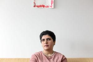 Azra Tayyebi istuu sohvallaan laajassa kuvassa. Pään yläpuolella näkyy hieman punaista piirustusta.