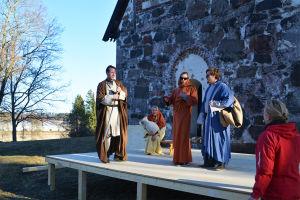 Fyra personer klädda i långa kåpor och kvinnorna i huvuddukar står på en scen uppbyggd framför Sibbo gamla kyrka.