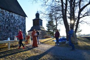 Sex personer står utanför Sibbo gamla kyrka. Vissa av dem är klädda i gammaldags kläder, långa kåpor och huvuddukar.