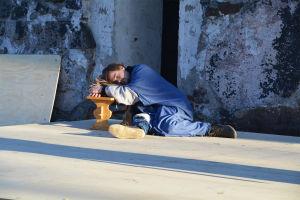 En man iklädd lång kåpa och blå mantel halvligger på en scen. Han har huvudet på en säck lutad mot en bänk och ser ut att sova.