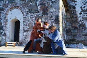 En kvinna och en man i gammaldags kläder håller i en man i mantel och försöker hindra honom från att stiga upp och gå iväg.