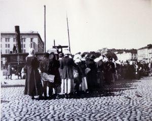 En svartvit bild av en lång brödkö på Salutorget i Helsingfors på 1910-talet.