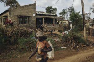 Mies kävelee myrskyn runtelemalla kylätiellä, taustalla on kaatunut puu ja talo.