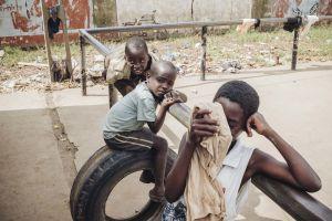 Kolme pikkupoikaa ja urheilukentän kaide: ensimmäinen pyyhkiä hikeä kasvoilta, toinen on autonrenkaan päällä ja kolmas makaa kaiteella.