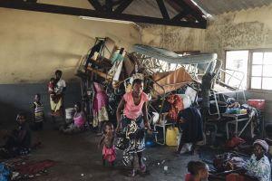 Kuvan keskellä on äiti ja lapsi hätämajoituskeskuksessa. Huoneen nurkassa on pulpetteja ja sänkyjä isossa kasassa.