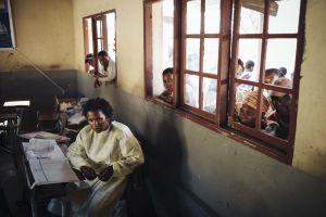 Hätämajoituskeskuksen klinikan työntekijä istuu keltainen suojakaapu päällä. Ihmisiä kurkkii ikkunoista hänen takanaan.