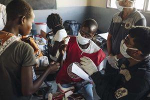 Punaisen Ristin vapaaehtoinen neuvoo vauvan äitiä lääkkeen annostelussa.