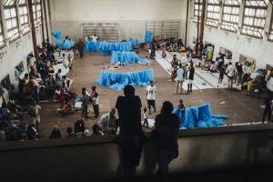 Näkymä koulun liikuntasalista, joka on Idai-myrskyssä kotinsa menettäneiden hätämajoituskeskus. Salissa on ihmisiä ja sinisiä hyttysverkkoja.