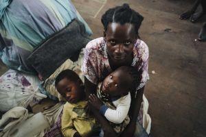 Äiti pitää kahta lastaan sylissä hätämajoituskeskuksen lattialla.