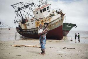 Äiti pitää tytärtään sylissä hiekkarannalla, taustalla ruosteisia aluksia.