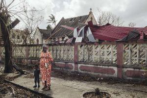 Raskaana oleva nainen ja poika seisovat kadulla. Taustalla hirmumyrsky Idain tuhoama rakennus.