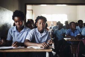 Koululaisia luokkahuoneessa Beirassa Mosambikissa. Suoraan kameraan katsoo nuori tyttö.